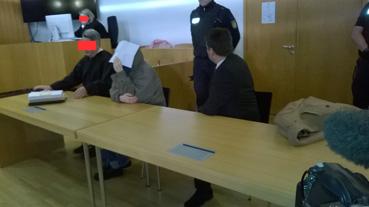Bild: Der Beschuldigte (mit Kladde vor dem Kopf )neben seinem Pflichtverteidiger